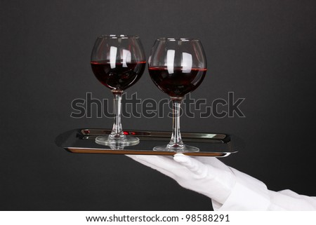 Hand in glove holding silver tray with wineglasses isolated on black