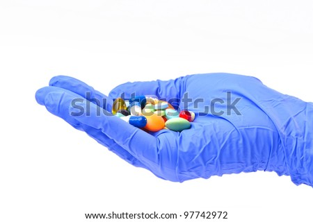 Hand in glove with colored pilsl isolated on white background.