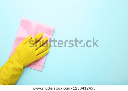 Hand in glove with rag on blue background #1233412453