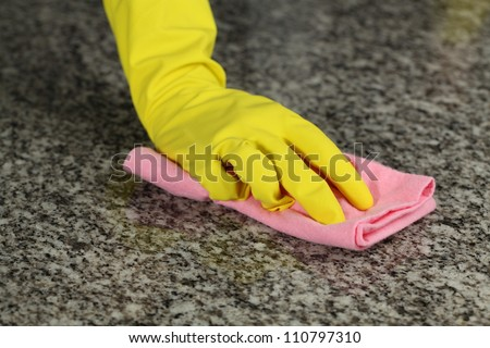 Hand in glove with rubber washing a floor