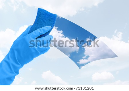 Hand in gloves cleaning the window with blue sponge