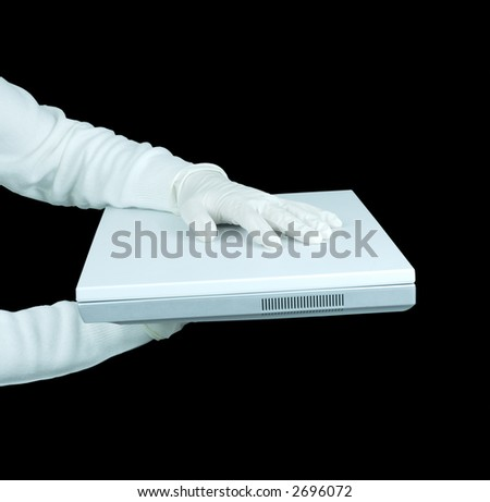 Hand in gloves handing over a white laptop