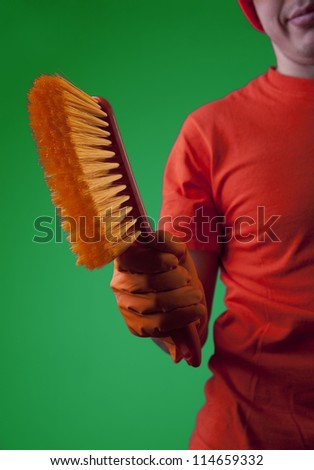 Hand in gloves holding red  broom  on green background