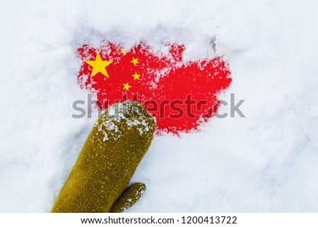 Hand in green mittens clean the flag of  China from snow. #1200413722