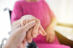 hand in hand, care giver holding hand of  old patient in hospital, dry and wrinkle skin, elderly health care
