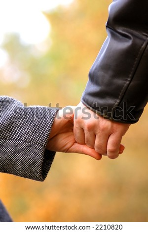 Hand-in-hand. Couple love in autumn scenery
