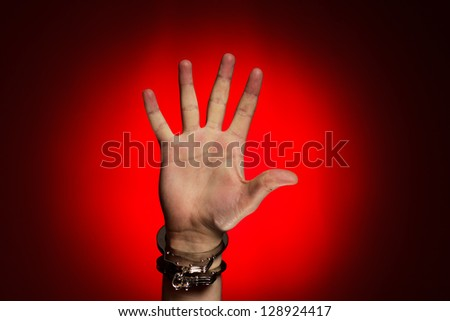hand in handcuffs over red background concept