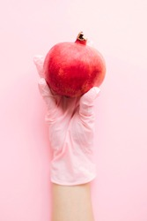 Hand in pink glove holding pomegranate on pink background flat lay. Order groceries and get them delivered safe during quarantine. Stay home Stay safe. Prevention of virus epidemic. Clean food