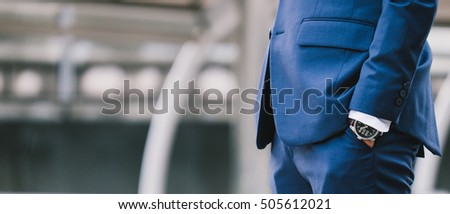 Hand in pocket with wrist watch in a business suit close up. soft focus
