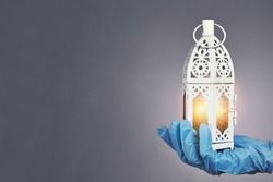 Hand in protective medical gloves holding traditional Arabic lantern with middle-eastern carving. Celebrating Holly month Ramadan 2020 in quarantine. A doctor celebrates Ramadan in hospital