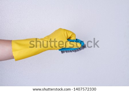 Hand in rubber glove using cleaning brush. Hand of house maid. Household chores concept. #1407572330