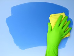 Hand in rubber glove wiping cloth surface