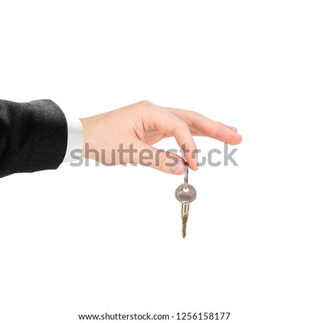 Hand in white shirt and black jacket holds keys. Isolated on white background