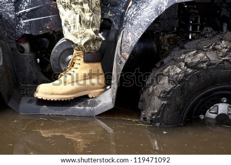 hand in yellow leather boot standing on the steps of the ATV standing in a muddy puddle