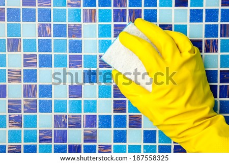 Hand in yellow protective glove cleaning mosaic wall with sponge