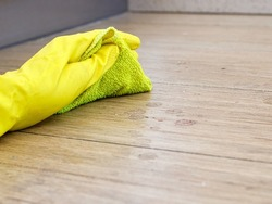 Hand in yellow rubber protective glove cleaning dirty filthy floor with micro fiber cloth from dust indoors, copy space, horizontal