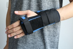Hand injury. Broken wrist and arm with bandage or immobilizer. Wrist pain from using computer or mobile phone. Office syndrome.Man using Thumb Splints to treat De Quervain's Tenosynovitis.Inflammation