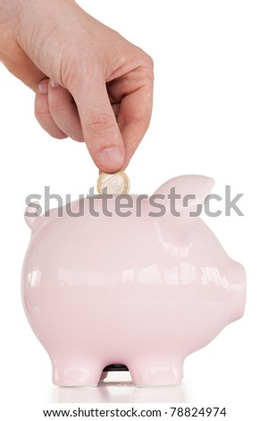 Hand inserting a coin in a pink piggy bank against a white background.