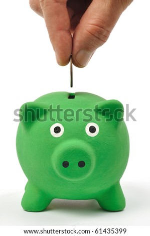 Hand inserting a coin into green piggy bank