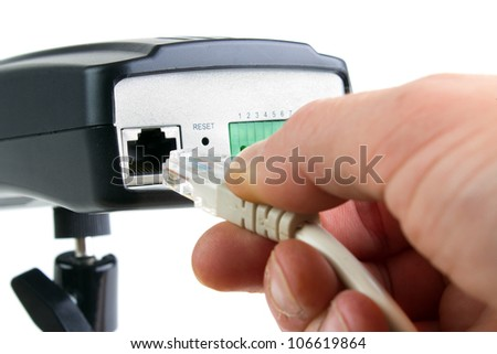 Hand inserting ethernet cable into network security camera, isolated on white