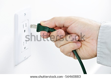 Hand inserting green electrical plug into outlet