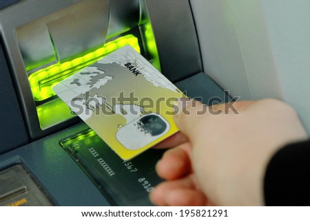 hand inserts the card into the ATM