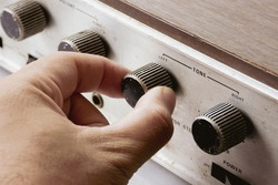 Hand is adjusting tone volume button of integrated amplifier vintage