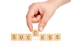 Hand is building the word success on white background