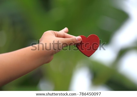 Hand is holding a small red heart #786450097