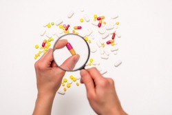 Hand is holding magnifier. Look through a magnifying glass at pills. Isolated on white background. Selective focus. Health, medicine and science concept. Top view