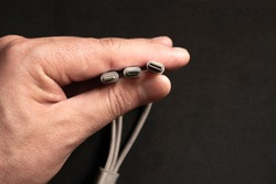 Hand is holding set of smartphone connectors: lightning, micro-usb and type-c cables on dark background.
