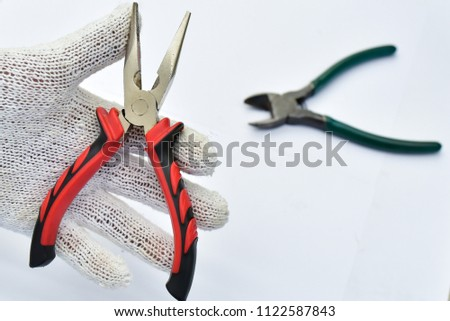 Hand is holding universal pliers on white background, hand hold needle Nose Pliers also known as pointy nose pliers or long nose pliers isolated,