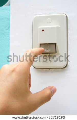 Hand is pushing an entrance electronic doorbell. This hand is left hand of man.