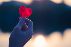 hand is raising the red paper heart with blur sunlight reflec on river ,Valentines day