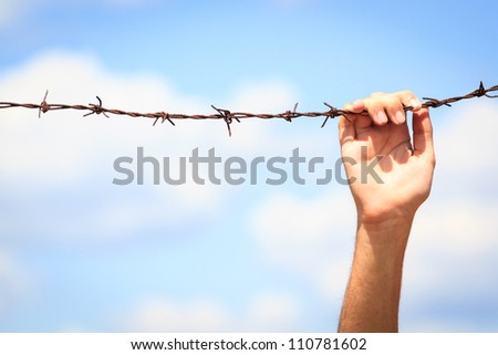 Hand is reaching fences against blue sky