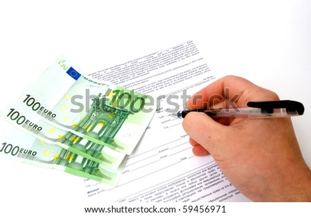 hand is signing the business document near money