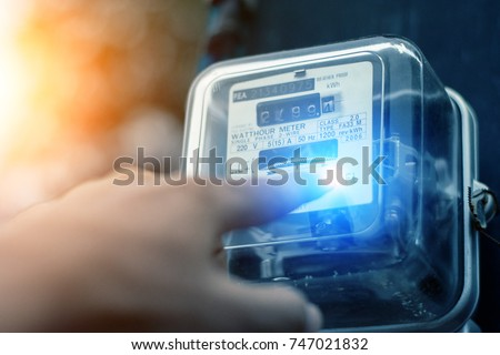 Hand is touching the transformer with copy space.Incorrect energy detection method.Watthour meter of electricity for use in home appliance.Electronics #747021832
