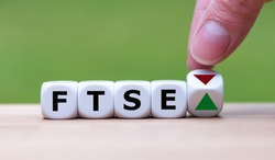 Hand is turning a dice and changes the direction of an arrow symbolizing that the FTSE 100 Index is changing the trend and goes up instead of down (or vice versa)