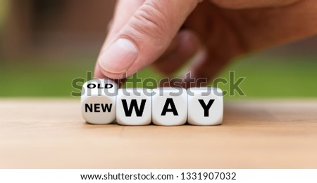 "Hand is turning a dice and changes the expression ""old way"" to ""new way"""