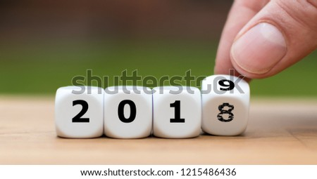 Hand is turning a dice and symbolically changes the year 2018 to 2019 #1215486436
