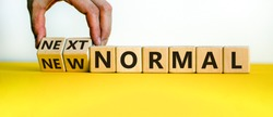 Hand is turning cubes and changes the words 'new normal' to 'next normal'. Covid-19 postpandemic concept. Beautiful yellow table, white background, copy space.