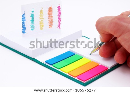 Hand is writing down on a note. - stock photo