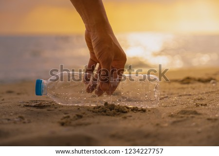 Hand Keep  cleanup  the Plastic bottle on beach at the sunset sc