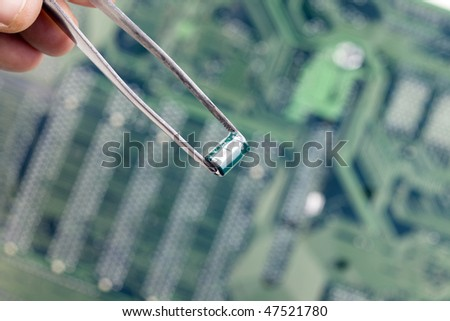 hand  keeping resistor from tweezers  - electronic circuits in background