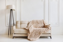 Hand knitted merino wool chunky blanket in interior on background. Stylish and cozy Scandinavian interior: bed, chair, white wall.