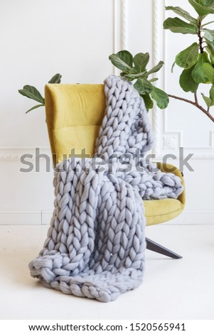 Hand knitted merino wool chunky blanket in interior on background. Stylish and cozy Scandinavian interior: bed, chair, white wall. Сток-фото ©