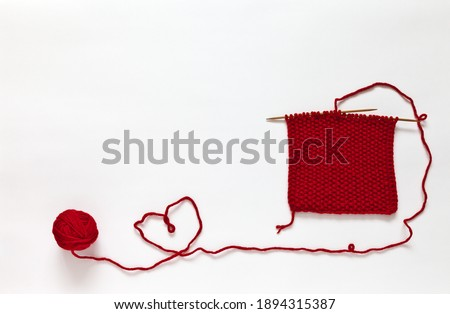 Hand knitting from woolen red yarn on white background. The thread is twisted in shape of heart. The knitting pattern is called 'rice'. Handmade gifts and DIY concept for Valentine's Day. Copy space Stock photo ©