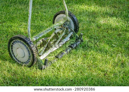 hand lawn mower close up with grass clips #280920386