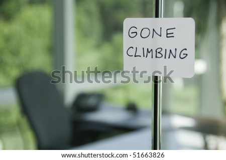 Hand-lettered sign on glass door to office: GONE CLIMBING (shallow field of depth)