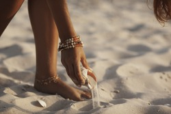 Hand lifting seashell from the sand on the beach outdoors. Female hand holding big seashell. Summertime concept.